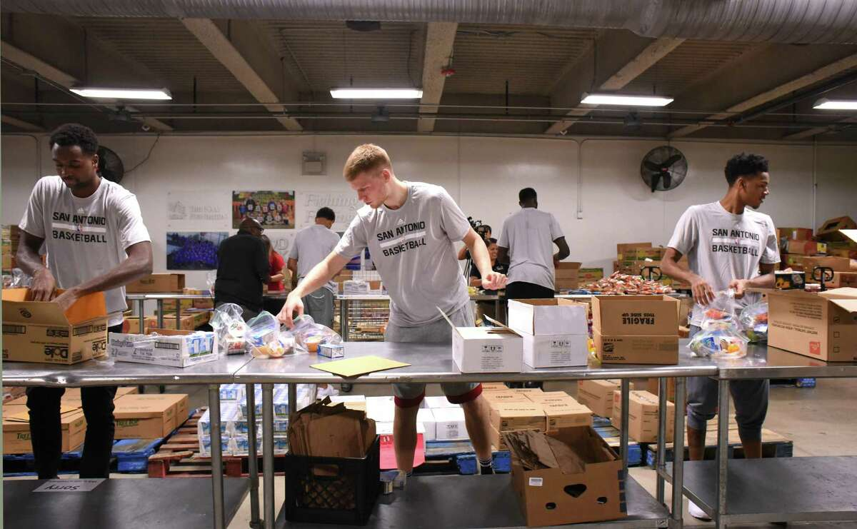 Livio Jean-Charles, left, Davis Bertans and Dejounte Murray of the San Antonio Spurs bag and pack food products for the San Antonio Food Bank BackPack Program on Wednesday, Aug. 31, 2016. The players filled gallon-size bags with snack items that students in need will take home to supplement meals on weekends. Schools participating in the program are chosen based on their rates of free or reduced lunch program participation or their access to services such as food pantries.