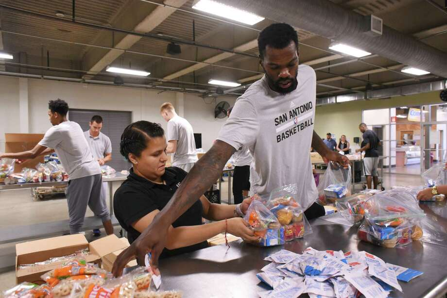 Five-foot-tall Daliah Contreras works beside San Antonio Spurs center Dewayne Dedmon bagging and packing food products for the San Antonio Food Bank BackPack Program on Wednesday, Aug. 31, 2016. The players and others filled gallon-size bags with snack items that students in need will take home to supplement meals on weekends. Schools participating in the program are chosen based on their rates of free or reduced lunch program participation or their access to services such as food pantries. Photo: Billy Calzada, San Antonio Express-News / San Antonio Express-News