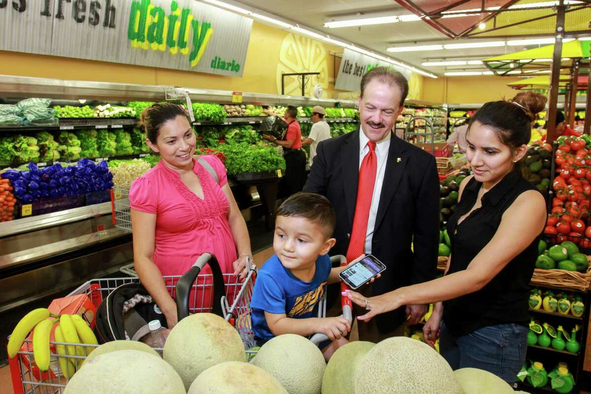 Fiesta CEO Mike Byars visits with shoppers Yessenia Garcia, left, and Belen Rivera with her two-year-old son, Adam, in the produce section at the grand re-opening of the Fiesta on Wayside Drive. Fiesta has invested in the store, redesigning and updating its appearance and layout, the first of several planned upgrades at the chain's stores. (For the Chronicle/Gary Fountain, August 31, 2016)