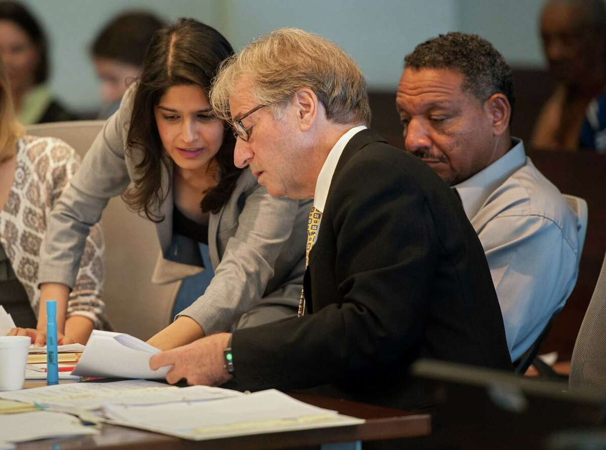 Attorneys Seema Saifee, left, and Barry Scheck confer as Darryl Howard looks on during a hearing Tuesday at the Durham County Courthouse.