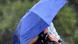 A man in downtown San Antonio shields himself from the rain as he crosses South Alamo Street on Wednesday afternoon, August 17, 2016.