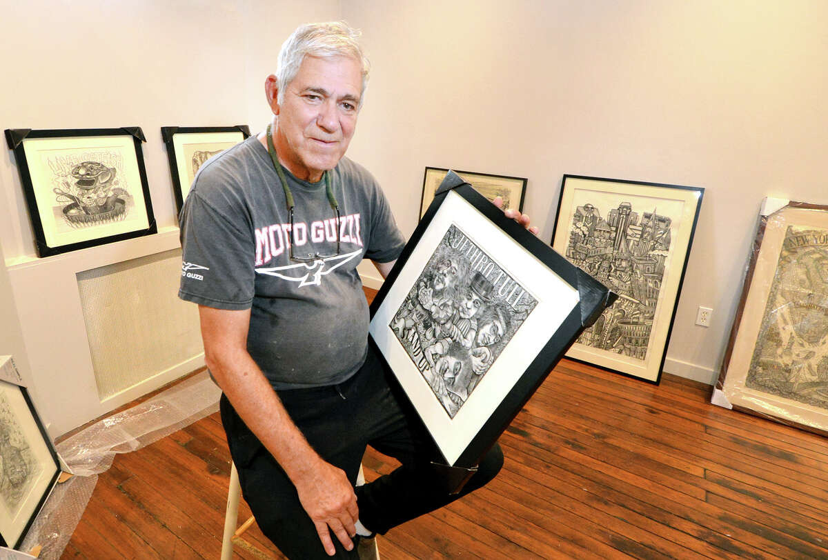 Artist James Grashow holds one of his wood carving prints on display this fall.