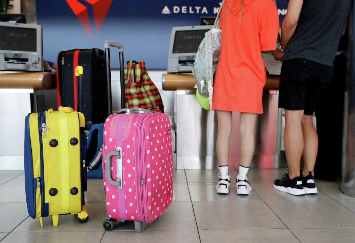 In this July 12, 2016, photo, passengers prepare to check bags at a Delta Air Lines counter at Baltimore-Washington International Thurgood Marshall Airport in Linthicum, Md. Delta Air Lines is rolling out new technology to better track bags throughout its system. (AP Photo/Patrick Semansky) ORG XMIT: MDPS301