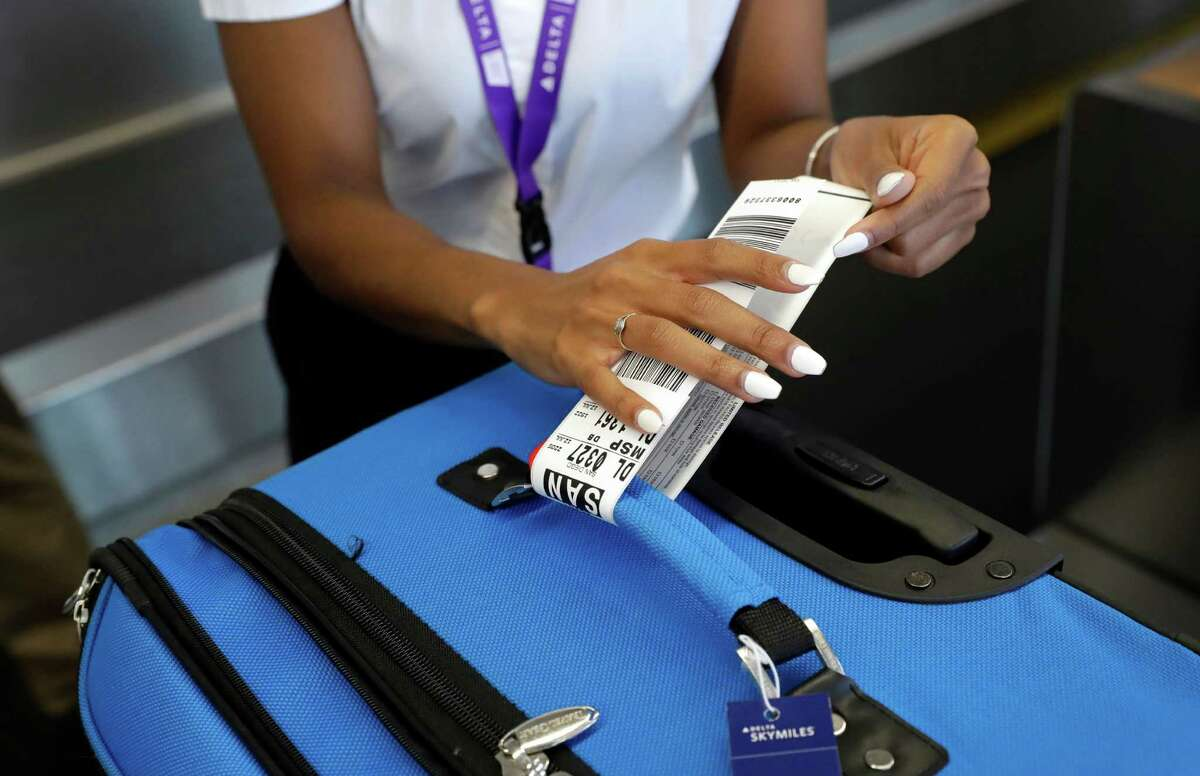 In this July 12, 2016, photo, Delta Air Lines employee Helen Evans places an RFID-enabled baggage tag on a passenger's checked bag at Baltimore-Washington International Thurgood Marshall Airport in Linthicum, Md. Delta Air Lines is rolling out new technology to better track bags throughout its system. (AP Photo/Patrick Semansky) ORG XMIT: MDPS302
