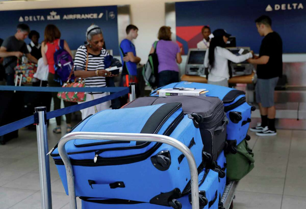 In this July 12, 2016, photo, bags wait to be checked at a Delta Air Lines counter at Baltimore-Washington International Thurgood Marshall Airport in Linthicum, Md. Delta Air Lines is rolling out new technology to better track bags throughout its system. (AP Photo/Patrick Semansky) ORG XMIT: MDPS303