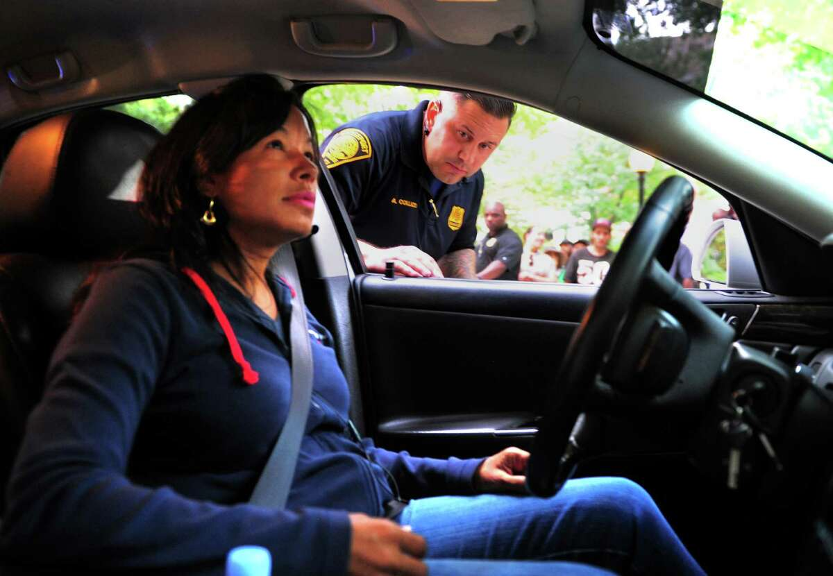 As part of a police stop demonstration, Bridgeport police officer Sgt. Angelo Collazo asks for the license and registration of a pulled over driver on Bank Street in Bridgeport, Conn., on Thursday Mar. 31, 2016. The driver is played by Carmen Velazquez. The event was part of a federal initiative sponsoring the demo: Project Longevity. Several different stop scenarios were played out to show people how to interact with police during stops.