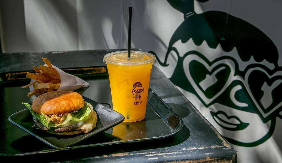 The burger with spicy corn chips and an apricot-orange drink at Locol in 2016. Photo: John Storey, Special To The Chronicle