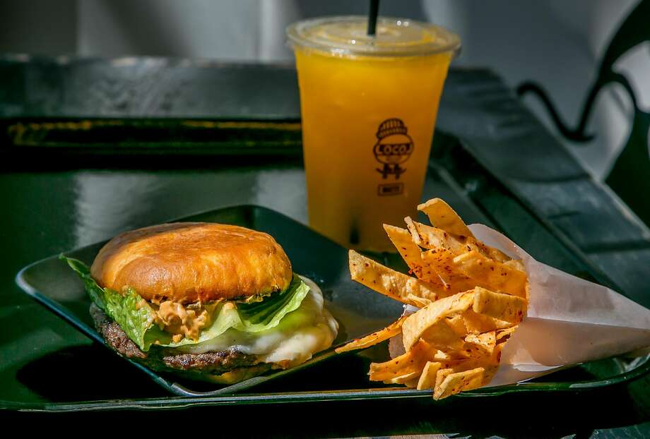The Cheeseburg ($5) with spicy corn chips and an apricot orange agua fresca at Locol in Oakland. Photo: John Storey, Special To The Chronicle