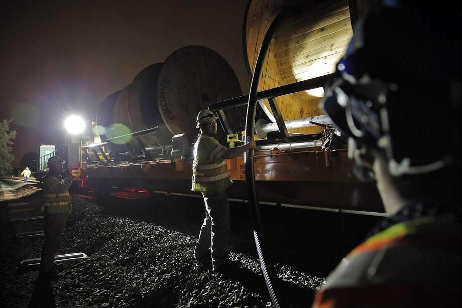 BART electrical foreworker Joe Skurski (center) guides a cable as the roll finishes on the BART tracks in Union City. Photo: Carlos Avila Gonzalez, The Chronicle
