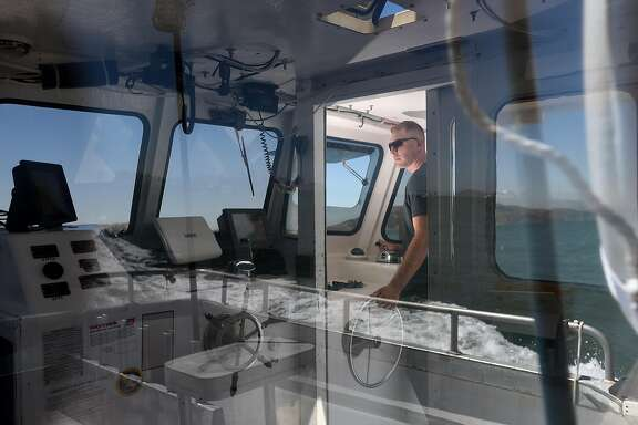 "Christian Cavanaugh sails his boat ""Chasin' Crustacean"" from Fort Baker to Sausalito for maintenance and fuel in the San Francisco Bay on August 31, 2016. Cavanaugh bought a boat and started running salmon fishing charter trips to make up for lost income due to algal blooms last season."