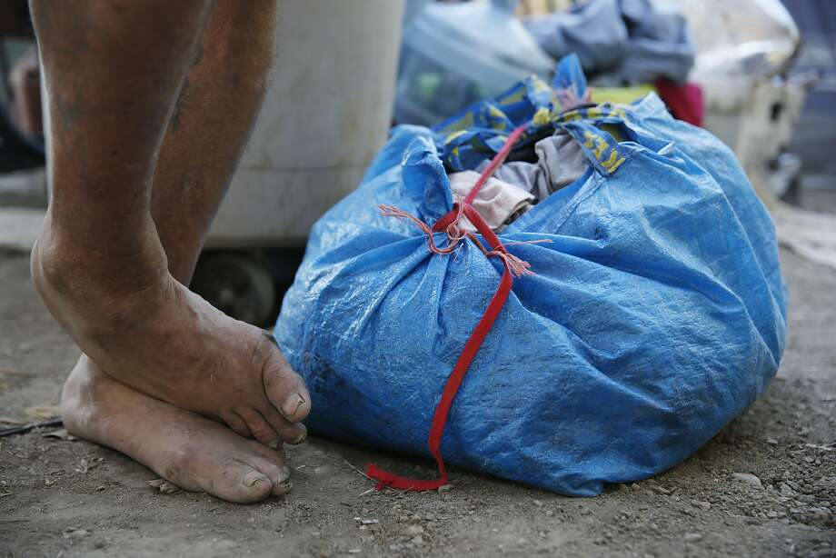 Pete Martinez stands next to a bag of laundry outside of his tent in San Jose. Photo: Lea Suzuki, The Chronicle