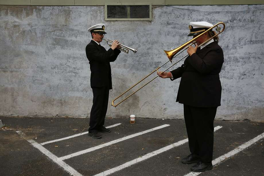 Aaron Priskorn (left) and Becca Burrington of the Green Street Mortuary Band warm up in a parking lot before taking part in a funeral procession. Photo: Leah Millis, The Chronicle