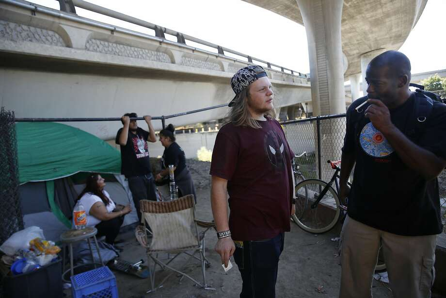 """Luke ( to r), 16, who says he's been homeless for """"about a year"""", and Anthony King, organizing fellow Sacred Heart Community Service, who is formerly homeless, talk as they stand near Luke's friends tent under Highway 280  on Tuesday, August 30,  2016 in San Jose, California. Photo: Lea Suzuki, The Chronicle"""