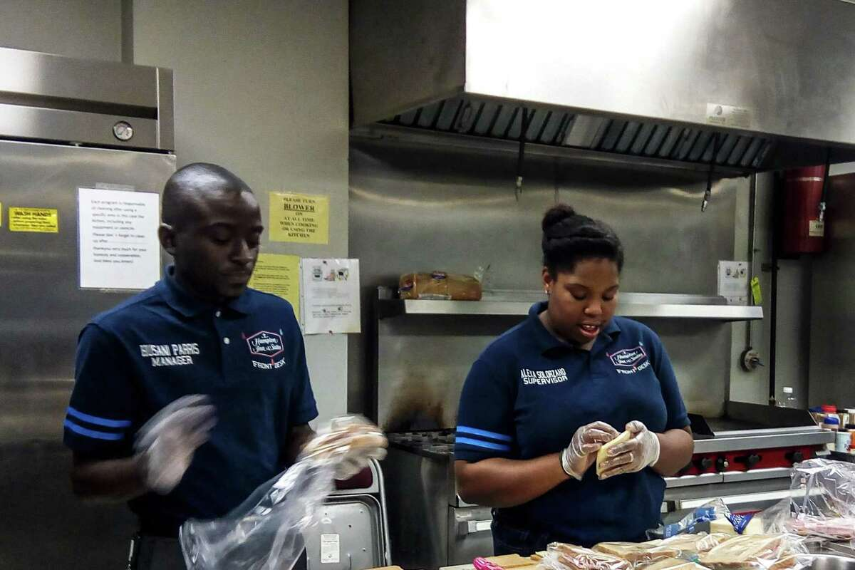 Husani Parris, front office manager, and Alexa Solorzano, front office supervisor, both of Hampton Inn & Suites by Hilton, Albany Downtown, who are doing volunteer work with the Albany Salvation Army. Each month volunteers convene at 9 a.m. ready to meet the Regional Food Bank delivery truck that provides 2,700 pounds of food. Volunteers unload the truck and stock the pantry for a month. Later, they prepare a lunch to be delivered to the homeless and needy with the Salvation Army's mobile feeding truck.