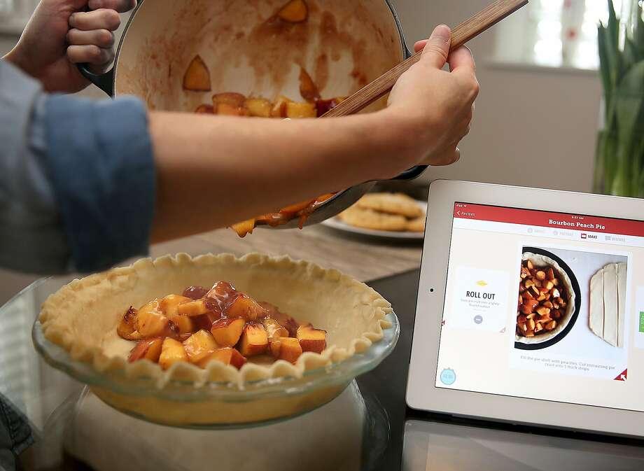 Entzel makes a bourbon peach pie as the Drop app shows instructions. Photo: Liz Hafalia, The Chronicle