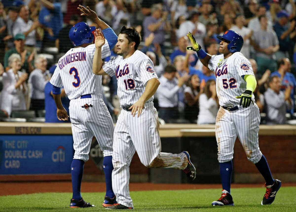 New York Mets' Curtis Granderson (3), Travis d'Arnaud (18) and Yoenis Cespedes (52) celebrate after all three scored on Kelly Johnson's eighth-inning double in the Mets' 5-2 victory over the Miami Marlins in a baseball game Wednesday, Aug. 31, 2016, in New York. (AP Photo/Kathy Willens) ORG XMIT: NYM128