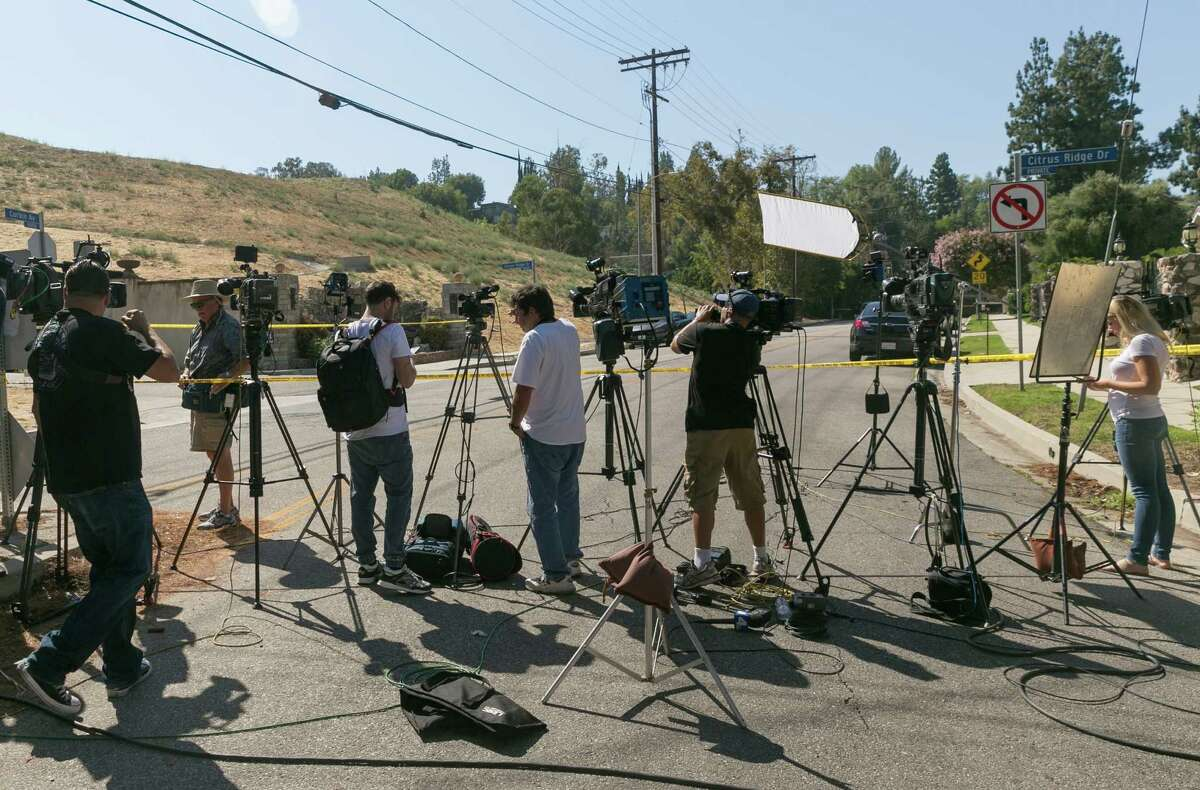 Members of the media wait outside singer Chris Brown's house in the Tarzana neighborhood of Los Angeles, Tuesday, Aug. 30, 2016. Police arrested Brown on Tuesday on suspicion of assault with a deadly weapon after a woman called hours earlier from outside his Los Angeles home and said she needed help. The arrest followed an hours-long standoff and lengthy search of Brown's home after police produced a search warrant. (AP Photo/Damian Dovarganes) ORG XMIT: CADD110