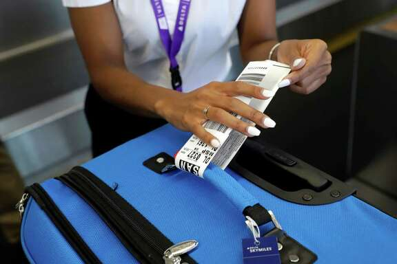 In this July 12, 2016, photo, Delta Air Lines employee Helen Evans places an RFID-enabled baggage tag on a passenger's checked bag at Baltimore-Washington International Thurgood Marshall Airport in Linthicum, Md. Delta Air Lines is rolling out new technology to better track bags throughout its system. (AP Photo/Patrick Semansky)