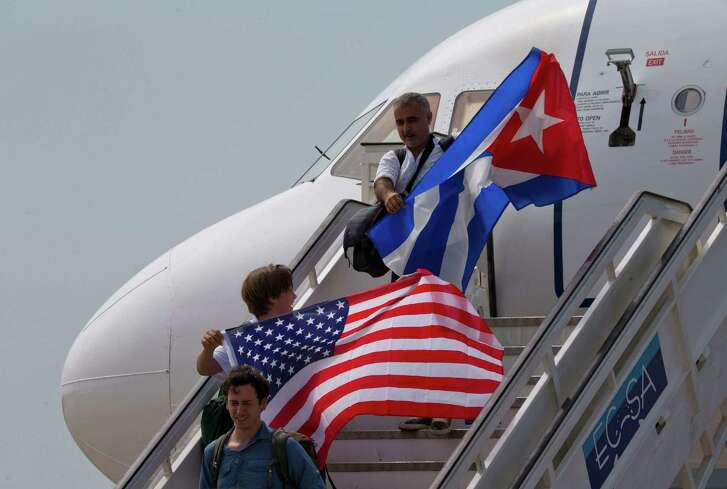 Two passengers deplane from JetBlue flight 387 waving a United States, and Cuban national flag, in Santa Clara, Cuba, Wednesday, Aug. 31, 2016. JetBlue 387, the first commercial flight between the U.S. and Cuba in more than a half century, landed in the central city of Santa Clara on Wednesday morning, re-establishing regular air service severed at the height of the Cold War. (AP Photo/Ramon Espinosa)