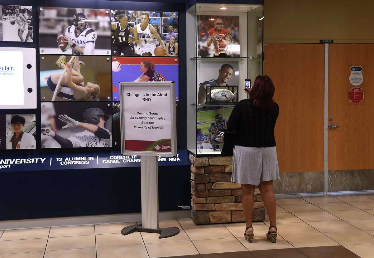 In this Tuesday, Aug. 30, 2016, photo, Mercedes Schmitte, from San Diego, takes a cell phone photo of the Colin Kaepernick memorabilia in the University of Nevada display at the Reno-Tahoe International Airport in Reno, Nev. Kaepernick's decision to sit during the national anthem is prompting protests over a display at the Reno airport. (Jason Bean/The Reno Gazette-Journal via AP) ORG XMIT: NVREN201