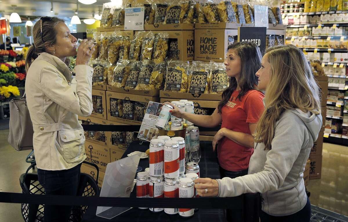 Caitlin Landesberg, right, founder and CEO of Sufferfest Beer Company, and Danni Zuralow, center, offer free samples of their Epic Pilsner and Taper IPA beers to Irina Luck, left, at Whole Foods in Potrero Hill in San Francisco, Calif., on Wednesday, August 31, 2016.