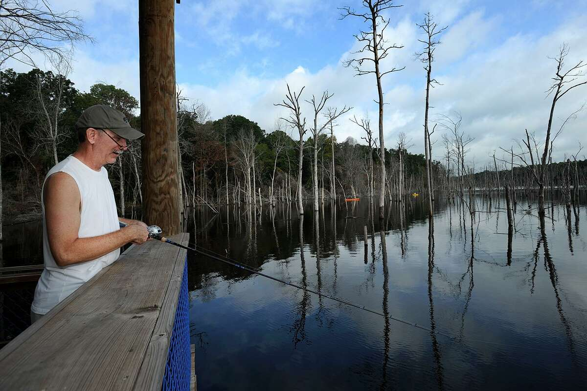Richard Self fishes from the fishing pier Saturday, Sept. 1, 2012, on opening day at Lake Naconiche Park north of Nacogdoches, Texas.