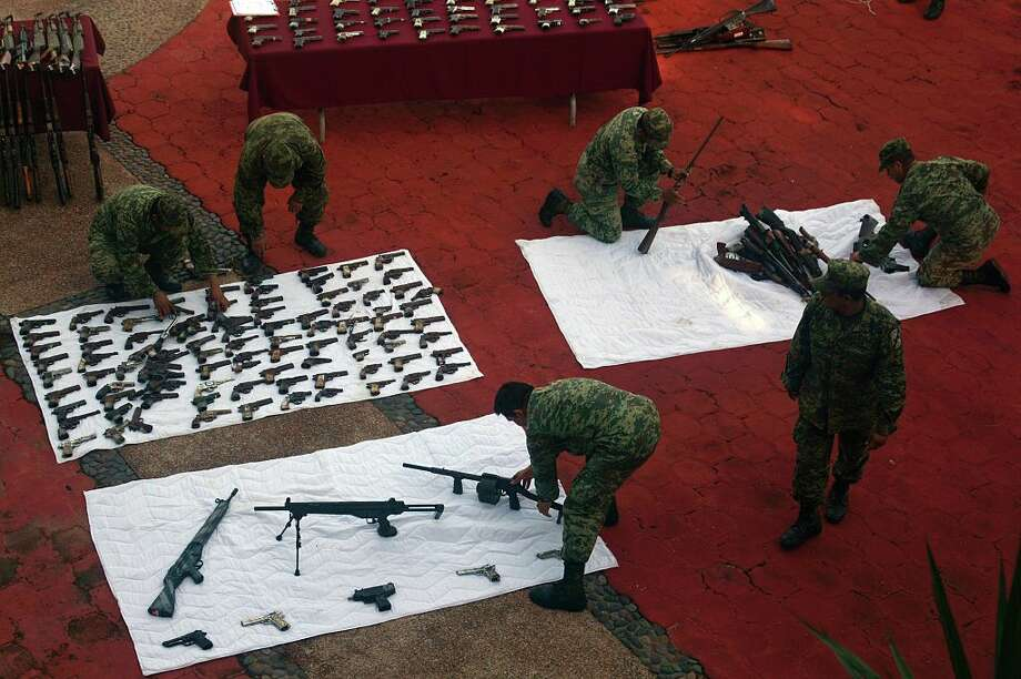 Soldiers display weapons seized during military operations to fight crime in Acapulco, Guerrero State, Mexico, on August 22, 2016.  Guerrero is one of Mexico's poorest and most violent states, where a lucrative drug trade has flourished. / AFP / Pedro PARDO        (Photo credit should read PEDRO PARDO/AFP/Getty Images) Photo: PEDRO PARDO/AFP/Getty Images