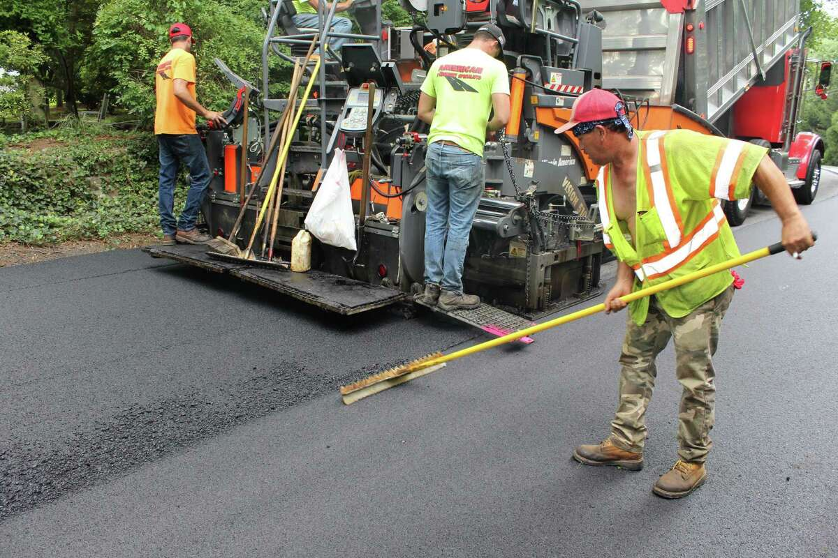 Workers from American Pavement Specialist, who are contracted by the city for paving work, lay down a fresh layer of asphalt on East Meadow Road.