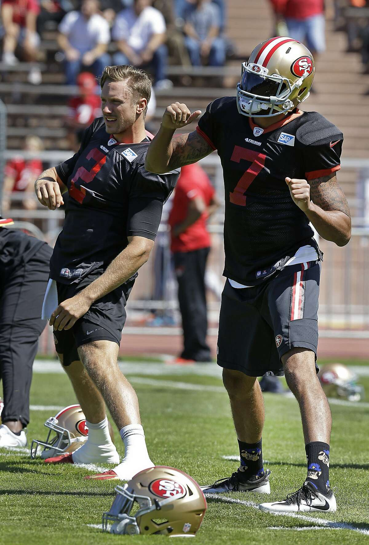 San Francisco 49ers quarterbacks Blaine Gabbert, left, and Colin Kaepernick (7) stretch during NFL football training camp, which was open to the public, Wednesday, Aug. 10, 2016, at Kezar Stadium in San Francisco. (AP Photo/Ben Margot)