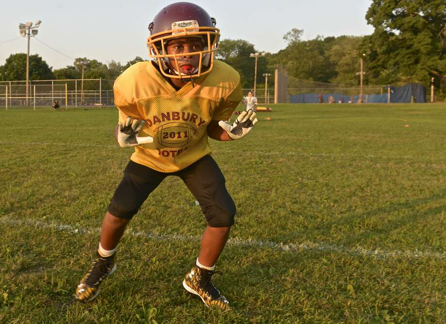 Cushan Perkins, 10, of Danbury, runs through a drill with the Danbury Trojans Pop Warner senior mites football team during a practice held in Rogers Park on Wednesday night, September 2, 2015, in Danbury, Conn. the teams season started with a game last Saturday and will continue through October. Photo: H John Voorhees III, Hearst Connecticut Media