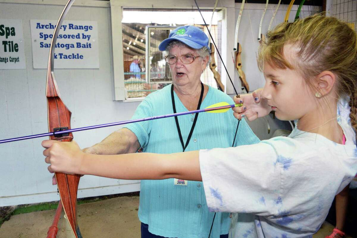 4H shooting sports instructor Glenda Smullen, left, helps Kari Gage of Ganesvoort with her archery skills during opening day at the Saratoga County Fair Tuesday July 19, 2016 in Ballston Spa, NY. (John Carl D'Annibale / Times Union)