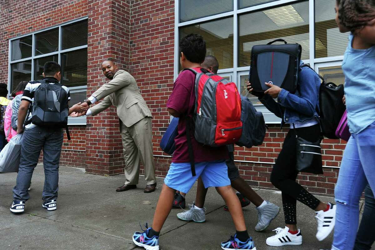 """Mark Glenn, of 100 Black Men of Stamford, welcomes students back to Dolan Middle School with high fives during the first annual """"Welcome Back to School Greeting"""" in Stamford, Conn. on Thursday, September 1, 2016. The 100 Black Men of Stamford is a non-profit community action organization comprised of successful men committed to improving the educational and economic conditions for African Americans and others in need."""