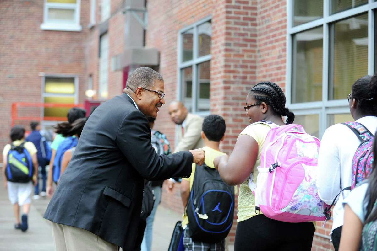 """Darwin Davis, of 100 Black Men of Stamford, welcomes students back to Dolan Middle School with high fives during the first annual """"Welcome Back to School Greeting"""" in Stamford."""