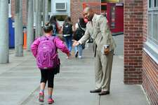 "Mark Glenn, of 100 Black Men of Stamford, welcomes students back to Dolan Middle School with high fives during the first annual ""Welcome Back to School Greeting"" in Stamford, Conn. on Thursday, September 1, 2016. The 100 Black Men of Stamford is a non-profit community action organization comprised of successful men committed to improving the educational and economic conditions for African Americans and others in need."