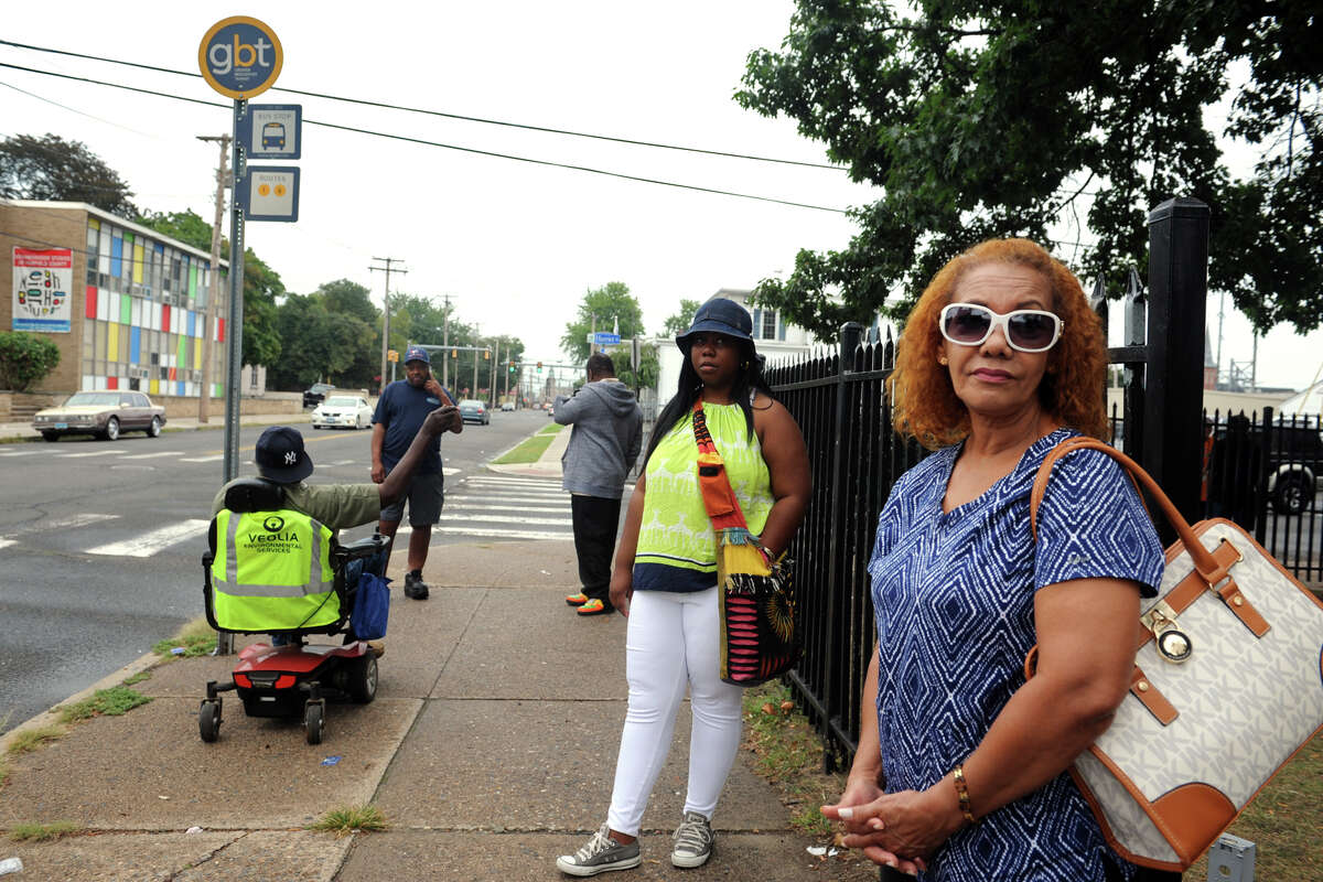 Angela Castillo, seen here right, waits for a bus with others at a bus stop on East Washington Avenue in Bridgeport on Thhursday. Castillo, who takes the bus home from work, said she had been waiting for over an hour.