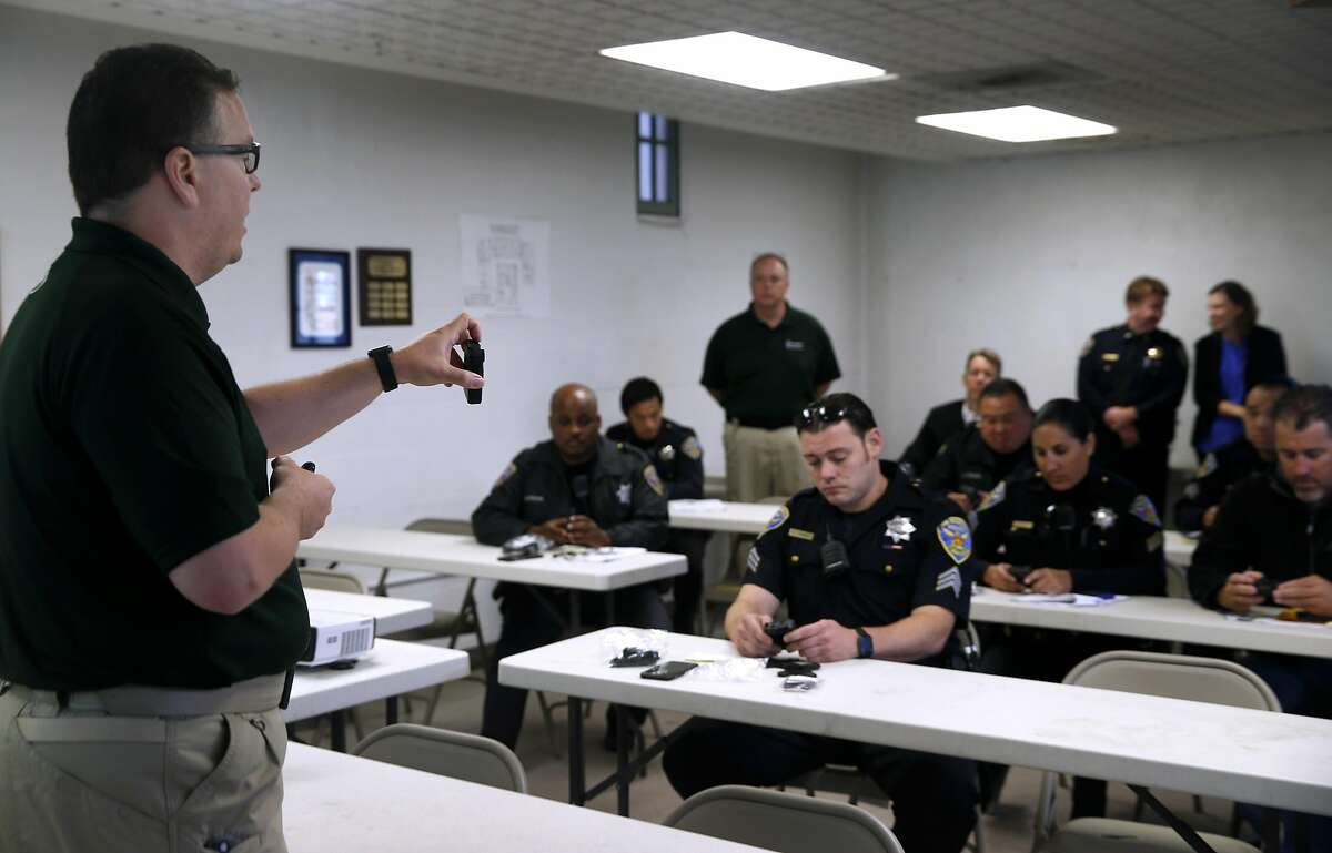 FILE-- Allan Kolak (left), an instructor with Taser International, trains police officers on the use of body worn cameras at the Ingleside police station in San Francisco on Sept. 1, 2016. The San Francisco Police Commission could vote Friday night whether to equip officers with Taser electroshock weapons, a proposal that has been debated and repeatedly rejected for nearly a decade.
