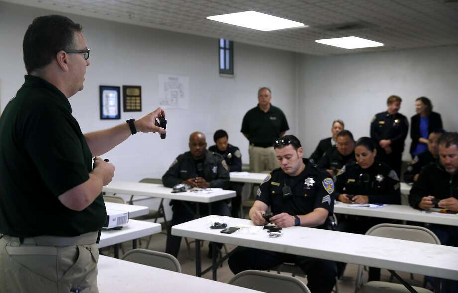 Allan Kolak (left), an instructor with Taser International, holds one of the company's body-worn cameras as he instructs police officers on how to use the devices at Ingleside Station in San Francisco. Photo: Paul Chinn, The Chronicle