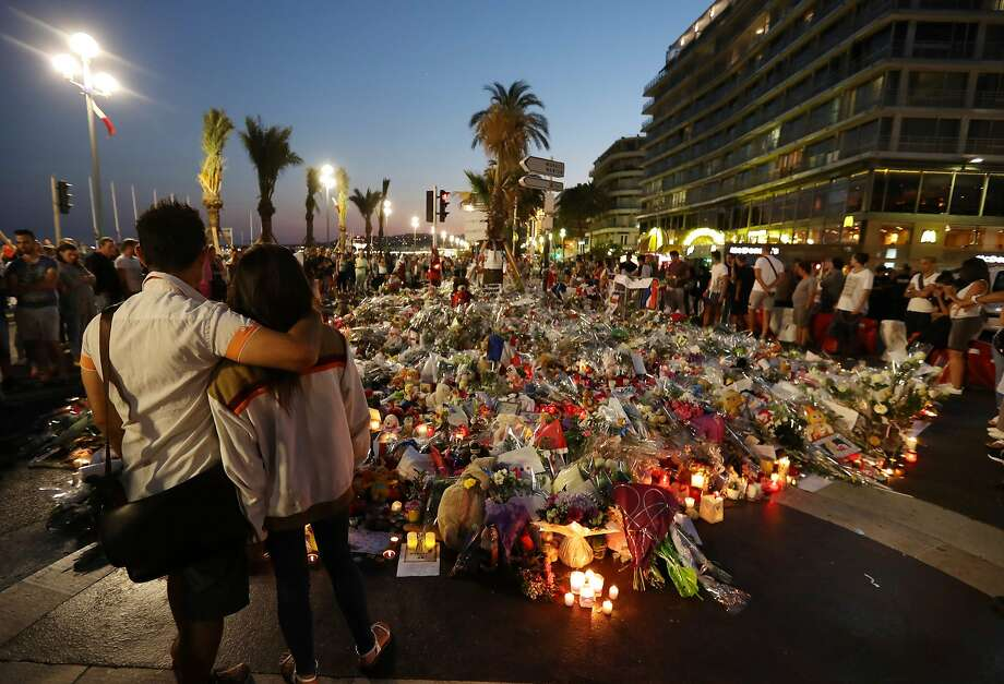 People stand in front of flowers, candles and messages at a memorial in Nice, France, four days after a man drove a truck through a crowd of Bastille Day celebrators killing 86 and injuring more than 400. Photo: VALERY HACHE, AFP/Getty Images