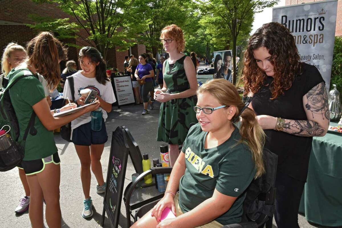 Rumors hair stylist Morgan Wheeler, right, braids Maddie Liguori's hair, 12, of Clifton Park as students sign up to win a spa day at Rumors salon as new students move into their dorms at Siena College on Thursday, Sept. 1, 2016 in Loudonville, N.Y. (Lori Van Buren / Times Union)