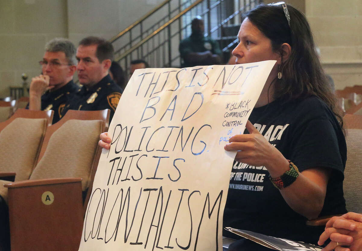 Marisa Laufer (right) holds a sign as police chief William McManus (left) and assistant chief Anthony Trevino (center) listen at City Council Chambers while a vote is taken to pass the police department's Collective Bargaining Agreement. Mayor Taylor voted for it, while only two council members voted against it.