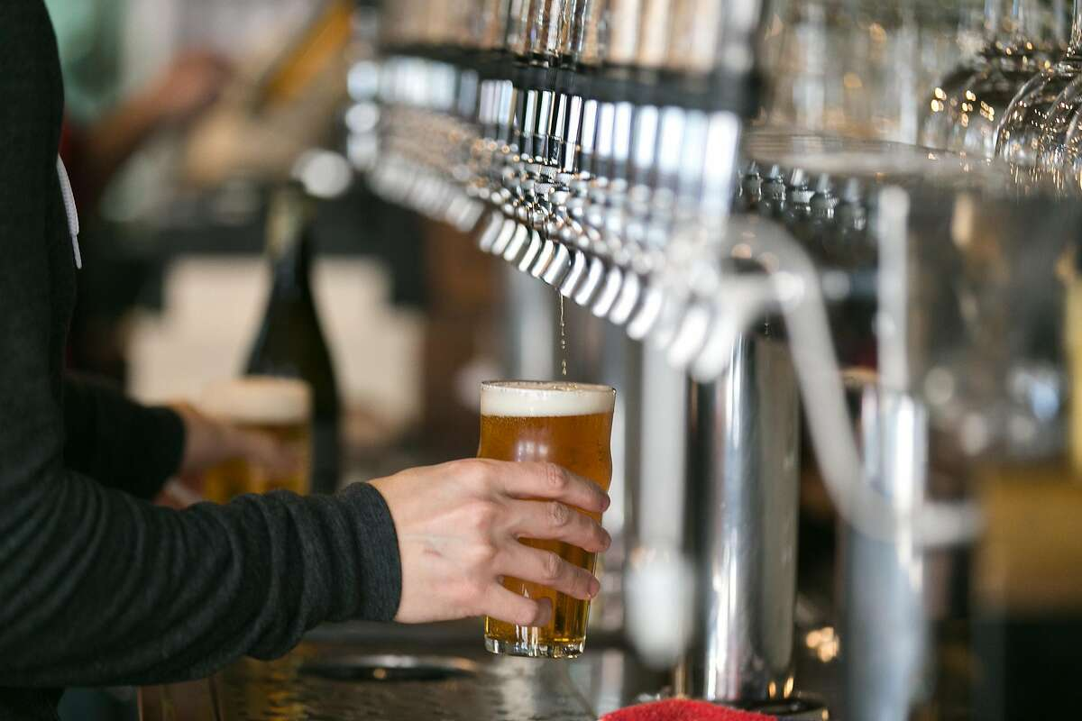 Monk's Kettle's general manager, Xian Choy, pours a beer from one of the 28 beers on tap.