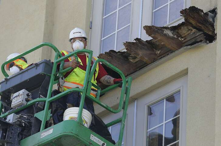 FILE - In this June 18, 2015, file photo, a crew works on the remaining wood of an apartment building balcony that collapsed killing six college students and injuring several others in Berkeley, Calif. California lawmakers are advancing a proposal aimed at making construction businesses more transparent after the Berkeley apartment balcony collapsed last year, killing six people.  (AP Photo/Jeff Chiu, File)