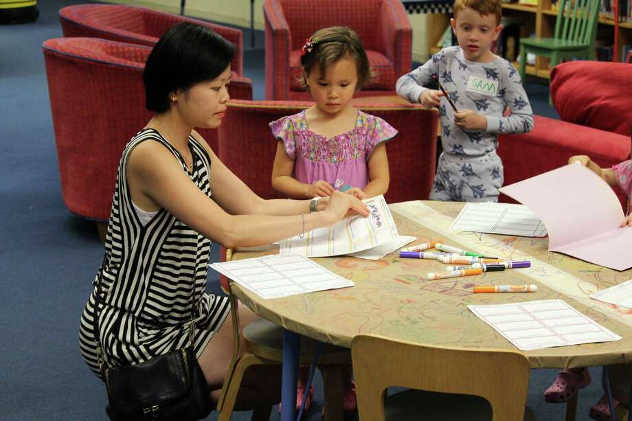 Valentina Belyaev and her mom Iris Belyaev work at the drawing station at the Westport Public Library's pajama party for incoming kindergartners on Aug. 25. Photo: Chris Marquette / Hearst Connecticut Media / Westport News