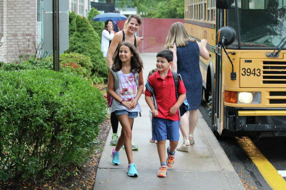 Fourth-grader Carolina Proctor and second-grader Alexander Proctor get off the bus at Coleytown Elementary School on the first day of classes on Thursday. Photo: Chris Marquette / Hearst Connecticut Media / Westport News