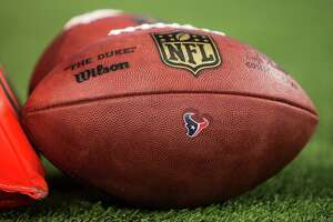 An NFL fotoball with a Houston Texans logo sits on the field before a pre-season football game against the Dallas Cowboys at AT&T Stadium on Thursday, Sept. 1, 2016, in Arlington, Texas.