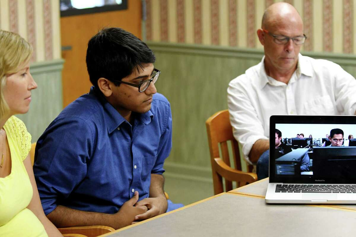 Unnas Hussain, an incoming senior at Shaker High School, center, watches a video that he helped to create on the North Colonie school district?'s new half-credit program where students can help other students with tech needs on Monday, Aug. 15, 2016, during an interview in Colonie, N.Y. With Hussain are; Lauren Sheeler, a Spanish teacher and dean for grades 11 and 12, left, and Gary Cimorelli, technology integration specialist for the district, right. (Will Waldron/Times Union)