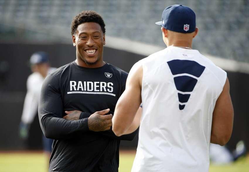Oakland Raiders' Bruce Irvin, left, chats with Seattle Seahawks' Jimmy Graham before a preseason NFL football game Thursday, Sept. 1, 2016, in Oakland, Calif. (AP Photo/Tony Avelar)