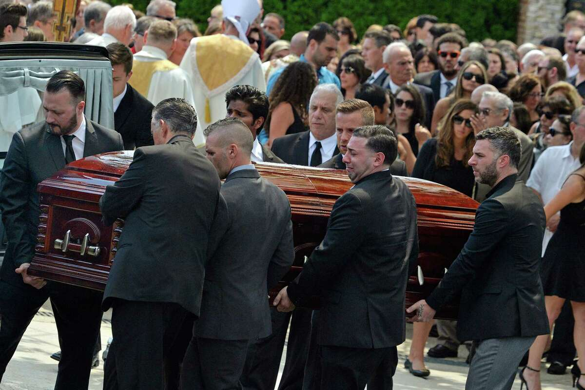 In this Aug. 6, 2016 file photo, mourners carry the casket of Karina Vetrano from St. Helen's Church following her funeral in the Howard Beach section of the Queens borough of New York. Detectives hunting for the person who strangled Vetrano in a secluded New York City marsh were encouraged after genetic material found beneath her fingernails, on her phone and on her neck resulted in a DNA profile of her probable attacker. A month later, their optimism has waned. The genetic fingerprint didn't match any of the profiles from convicted criminals in the state's Combined DNA Index System. A check against the FBI's DNA database also came up empty. (Steven Sunshine /Newsday via AP)