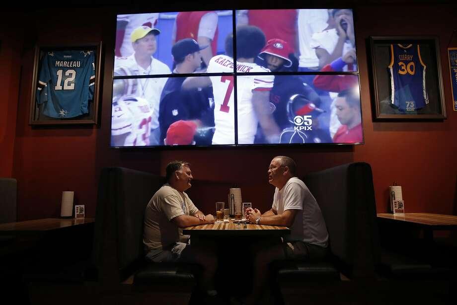 Jeff Reagor (left) and Kevin Bixel, both of Turlock, watch at Hauck's Grill as the national anthem is played on the big screen, moments before the San Francisco 49ers take on the San Diego Chargers in preseason action. Kaepernick kneels, as does teammate Eric Reid, during the patriotic display. Photo: Michael Macor, The Chronicle