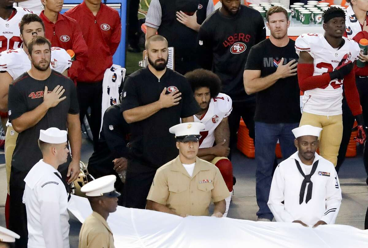 San Francisco 49ers quarterback Colin Kaepernick, middle, sits during the national anthem before the team's NFL preseason football game against the San Diego Chargers, Thursday, Sept. 1, 2016, in San Diego. (AP Photo/Chris Carlson)